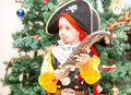 Little boy child dressed as pirate for Halloween  on background of Christmas tree. Royalty Free Stock Photo