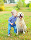 Little boy child kissing Golden Retriever dog on grass Royalty Free Stock Photo