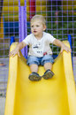 Little boy on a children's slide in the park on a walk Royalty Free Stock Photo