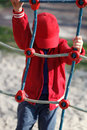 Little boy climbing on rope at playground in red cap Stock Images