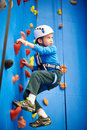 Little boy is climbing in sport park on blue wall Royalty Free Stock Photo