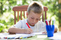 Little boy coloring outside Royalty Free Stock Photo