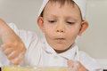 Little boy concentrating as he bakes a cake carefully stirring the mixture in the mixing bowl after adding some flour Stock Photography