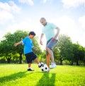 Little boy die voetbal met zijn vader spelen Stock Foto's