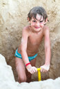 Little boy digging in the sand on a tropical beach Royalty Free Stock Photo