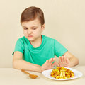 Little boy does not want to eat fried potatoes a Royalty Free Stock Images