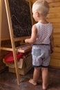 Little boy drawing with chalk on a blackboard