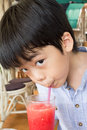 Little boy is drinking juice using straw Royalty Free Stock Photos
