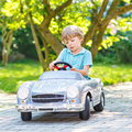 Little boy driving big toy old car outdoors preschool vintage and having fun active leisure with kids on warm summer day Stock Images