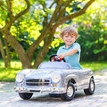 Little boy driving big toy old car outdoors preschool vintage and having fun active leisure with kids on warm summer day Royalty Free Stock Photos