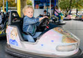 A little boy driving a bumper car at the carnival Stock Image