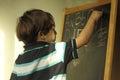 A little boy writing on an easel