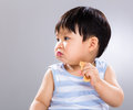 Little boy eat biscuit and look aside with gray background Stock Photo