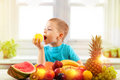 Little boy eating apple with fruits in kitchen Royalty Free Stock Photo