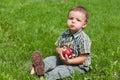 Little boy eating apple outside Stock Images