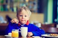 Little boy eating breakfast in cafe Royalty Free Stock Photo