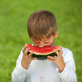Little boy eating a fresh watermelon Stock Photos