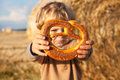 Little boy eating German pretzel on goden hay field Royalty Free Stock Image