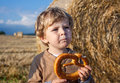 Little boy eating german pretzel on goden hay field in summer Royalty Free Stock Images
