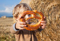 Little boy eating german pretzel on goden hay field in summer Royalty Free Stock Photos