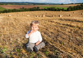 Little boy eating German sausage on goden hay field Royalty Free Stock Photo