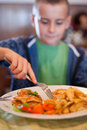 Little boy eating in a restaurant Royalty Free Stock Image