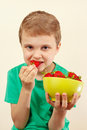Little boy eating sweet strawberries from bowl a Stock Image