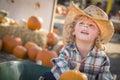 Little boy en el vaquero hat en el remiendo de la calabaza Imagen de archivo