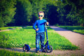 Little boy enjoy riding scooter in summer nature Stock Photography