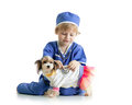 Little Boy Examining Puppy Dog...