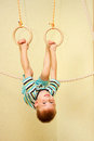 Little boy exercising on gymnastic rings playing sports at sport center kid Royalty Free Stock Images