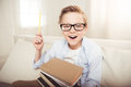 Little boy in eyeglasses holding pile of books and pointing up with pencil Royalty Free Stock Photo