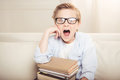 Little boy in eyeglasses sitting with books and looking at camera with open mouth Royalty Free Stock Photo