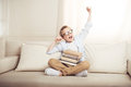 Little boy in eyeglasses sitting on sofa with books stretching and yawning Royalty Free Stock Photo