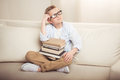 Little boy in eyeglasses sitting on sofa with pile of books and looking away Royalty Free Stock Photo
