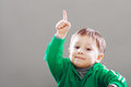 Little boy finger upward with idea showing over grey backgound Royalty Free Stock Images