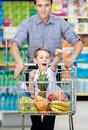 Little boy with fists up sitting in shopping trolley suiting food father drives the cart Royalty Free Stock Photos