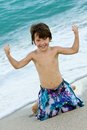Little boy flexing muscles on beach elementary aged wearing swimming trunks Stock Photo