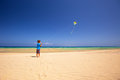Little boy flies a kite on a beach, Fuerteventura, Canary Islands, Spain Royalty Free Stock Photo