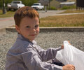 Little Boy with Garbage Bag Outside Stock Image