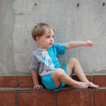 Little boy gesturing in the backyard and pointing his finger to a direction Royalty Free Stock Image