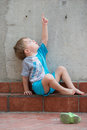 Little boy gesturing in the backyard and showing how high airplane is flying that just passed sky above his head Royalty Free Stock Image