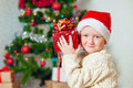 Little boy with gifts near a christmas tree in santa hat Royalty Free Stock Photos