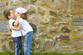 Little boy girl kissing front stone wall Royalty Free Stock Images