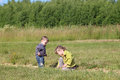 Little boy and girl paly on grass at green meadow Royalty Free Stock Photo