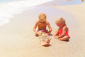 Little boy and girl play with water on beach Royalty Free Stock Photo