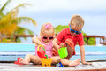 Little boy and girl playing in swimming pool at Royalty Free Stock Photo