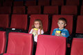 Little boy and girl with popcorn watching a movie Royalty Free Stock Photo