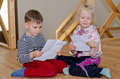 Little boy and girl sitting together reading on a wooden floor each a letter or note on a sheet of paper with serious engrossed Royalty Free Stock Photography