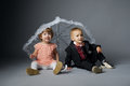 Little boy and girl sitting under umbrella